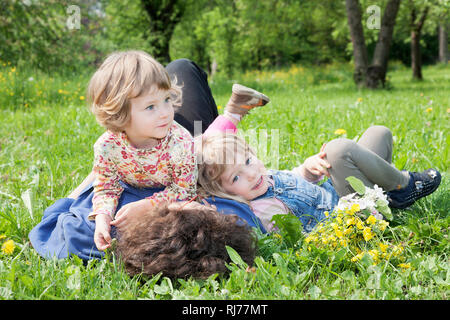 2 Mädchen, 5 und 3 Jahre alt, spielen mit der Mutter auf einer Frühlingwiese - Stock Photo