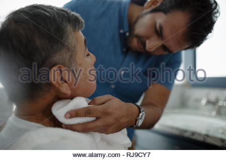 Latinx son shaving senior father s face - Stock Photo