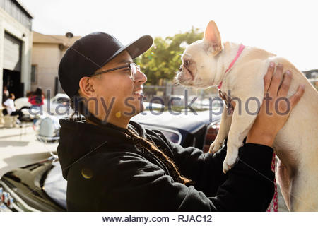 Latinx young man holding French bulldog in sunny parking lot - Stock Photo
