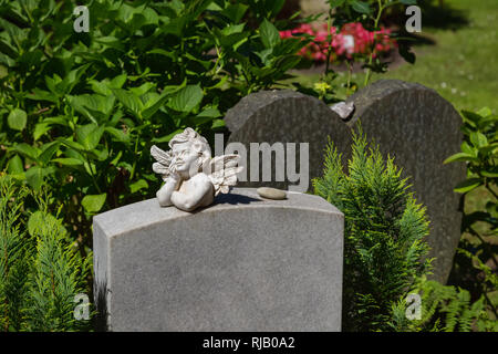 Little angel with wings lies on a marble tombstone - Stock Photo