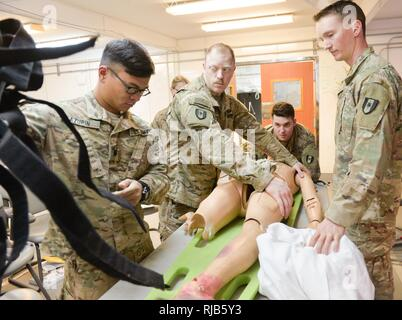 U.S. Army Soldiers, 28th Combat Support Hospital, prepare to remove a simulated trauma patient from a backboard during the Trauma Nursing Core Course hosted by the 28th CSH near Baghdad, Iraq, Nov. 2, 2016. This is the first time TNCC, a highly sough-after trauma training course for nurses, has been conducted by a unit deployed in support of Operation Inherent Resolve. Effective and comprehensive training is key for deployed medical personnel to preserve the health of Coalition forces working to weaken and defeat Islamic State in Iraq and the Levant. Combined Joint Task Force-Operation Inheren - Stock Photo