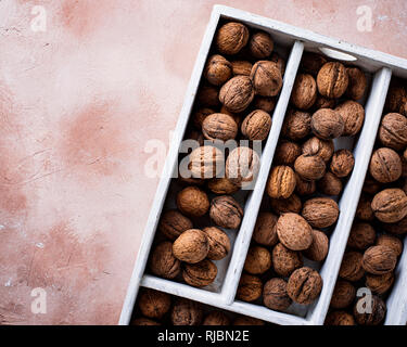 Walnuts in wooden box on lignt brown background - Stock Photo