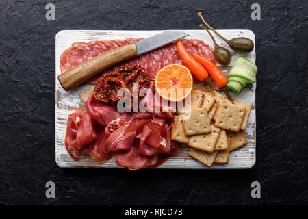Italian antipasti snacks set. Capers, prosciutto, salami and crackers over black grunge table, top view. Food photography - Stock Photo