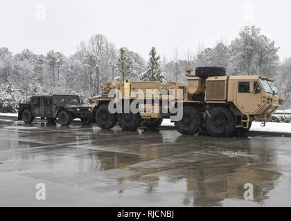 U.S. Soldiers with the Field Maintenance Shop 5 Vehicle Recovery Team, South Carolina National Guard, help assist Highway Patrol with vehicle recovery during a snow storm in Rock Hill, South Carolina, Jan. 17, 2018. The Soldiers were on standby for any calls received by the Highway Patrol of vehicles that become stuck, abandoned, or block access to the roadways. - Stock Photo