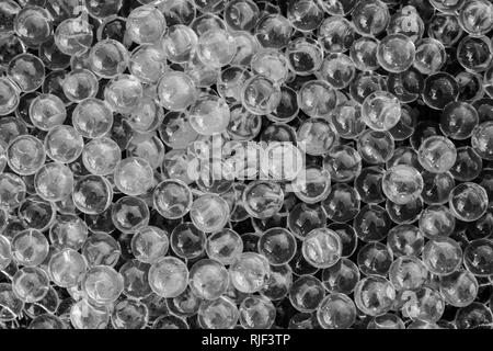 Water black and white gel balls with bokeh. Polymer gel. Silica gel. Balls of black and white hydrogel. Crystal liquid ball with reflection. Black and - Stock Photo