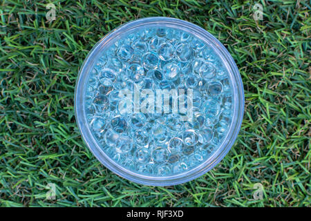 Blue gel balls in the middle on green artificial grass background. - Stock Photo