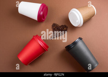 top view heart of coffee beans and various coffee drinks in paper disposable cups flat lay brown background, mock up blank paper cups - Stock Photo