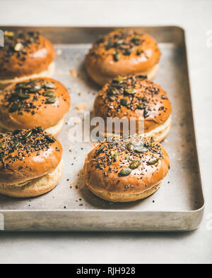 Freshly baked homemade buns with seeds for cooking burgers - Stock Photo