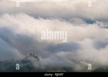 Famous Gergeti Trinity Church near Stepantsminda in the clouds, Georgia, Caucasus. - Stock Photo
