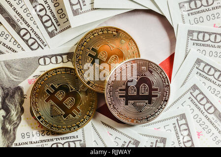 Gold and silver bitcoins on hundred-dollar American bills. - Stock Photo