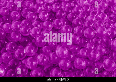 Water purple gel balls with bokeh. Polymer gel. Silica gel. Balls of purple hydrogel. Crystal liquid ball with reflection. Purple balls texture backgr - Stock Photo