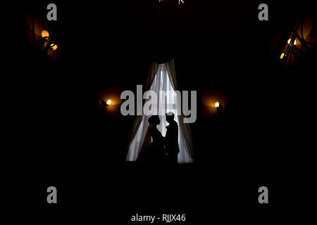happy luxury bride and groom standing at window light in rich room, tender moment - Stock Photo