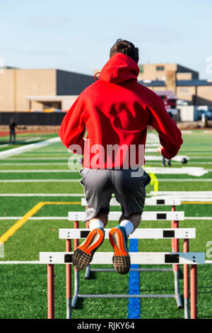 A high school athlete is jumping over hurdles on a green turf field as part of strength and agility practice. - Stock Photo