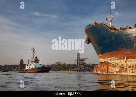 Tugboat pulls container ship into position - Stock Photo
