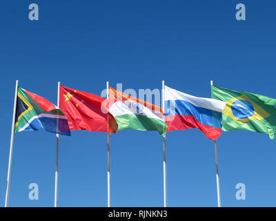 Waving flags of the BRICS countries against the blue sky. The summit of Brazil, Russia, India, China and South Africa - Stock Photo