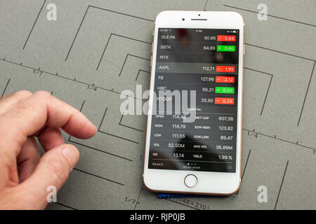 PARIS, FRANCE - SEP 26, 2016: Male hand holding New Apple iPhone 7 8 Plus smartphone after unboxing and testing by installing the app application software Stocks market with Aapl stock price  - Stock Photo