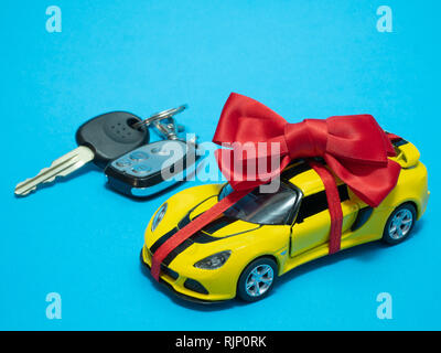 small yellow toy car with red bow on blue. auto keys blurred on background - Stock Photo