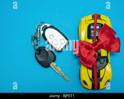 small toy yellow sport car with bow and keys on blue background. view from top. flat lay - Stock Photo