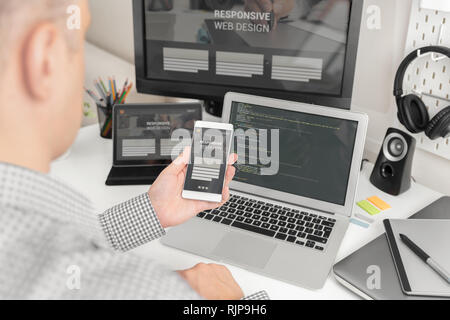Web designer, programmer working with responsive web template. Multiple devices on desk. - Stock Photo