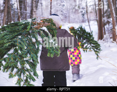 Boy and girl walking through snow covered forest carrying christmas tree, rear view - Stock Photo