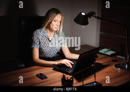 Portrait of stressed businesswoman sitting at office desk - Stock Photo
