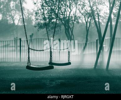 Swings in public park on a misty morning. UK - Stock Photo
