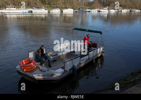 Two passengers on Hammerton's Ferry, cross the river Thames between Marble Hill House on the north bank, and Ham on the southern bank, on 3rd February 2019, in London, England. Hammertons Ferry was originally opened in 1908 by Walter Hammerton and its current owners are Mr & Mrs Francis Spencer in July, 2003. The whole family are currently involved in all aspects of the business, however the daily running of the Ferry is by father & son, Francis & Andrew Spencer. Hammerton's is a pedestrian and cycle ferry service across the River Thames in the London Borough of Richmond upon Thames, London - Stock Photo