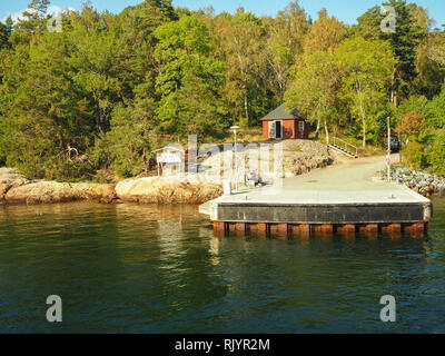 Landing stage, rocky coast and pine trees on Grinda island in the Stockholm Archipelago, Sweden - Stock Photo