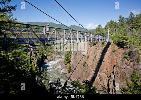 WY03373-00...WYOMING - Hiker crossing suspension bridge over the Yellowstone River on the Hellroaring Creek Trail in Yellowstone National Park. - Stock Photo