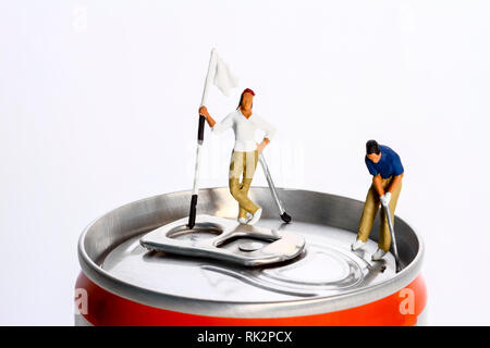 Conceptual diorama image of a miniture figure couple playing golf on a drinks can - Stock Photo