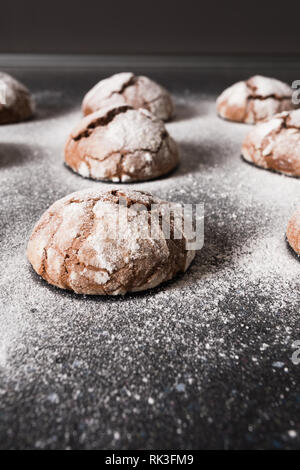 Delicious chocolate chip cookies with beautiful cracks and dusted with icing sugar on a dark background. - Stock Photo