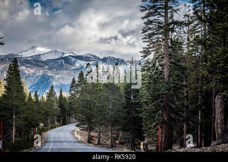 Looking down the road California State Route 203 in Mammoth Lakes, with the Sierra Nevada Mountains in the distance - Stock Photo