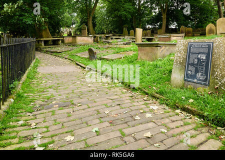 Cobbled path, information plaque (Brontes) headstones & graves in churchyard - St Michael & All Angels Church, Haworth, West Yorkshire, England, UK. - Stock Photo