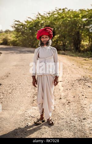 Rajasthani man wearing white traditional dress and red turban - Stock Photo