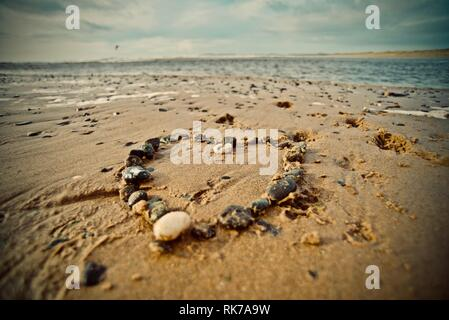Love the beach, love the sea. A heart made of pebbles on the sand of a beach with the tide coming in, Rhosneigr, Anglesey, North Wales, UK - Stock Photo