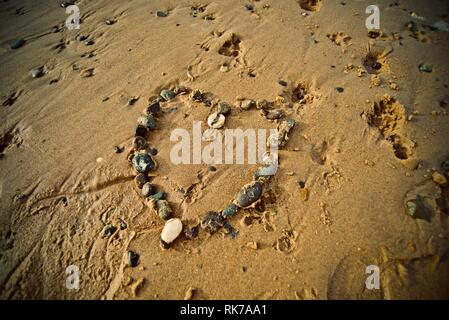 A heart made of pebbles on the sand of a beach with the tide coming in, Rhosneigr, Anglesey, North Wales, UK - Stock Photo