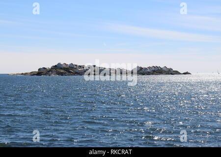 Die Insel Åstol an der Westküste Schwedens - Blick von der Fähre auf Åstol mit seinen Häusern und dem kleinen Naturhafen - Stock Photo