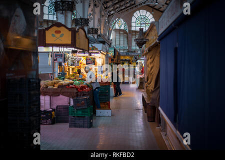 Traders unload fresh fruit and vegetables from crates as they get ready for a busy day at the central market, mercado central, in Valencia, Spain. - Stock Photo