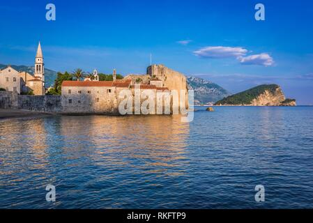 Old Town with bell tower of Saint John the Baptist cathedral in Budva city on Adriatic Sea coast in Montenegro. Sveti Nikola island on background. - Stock Photo