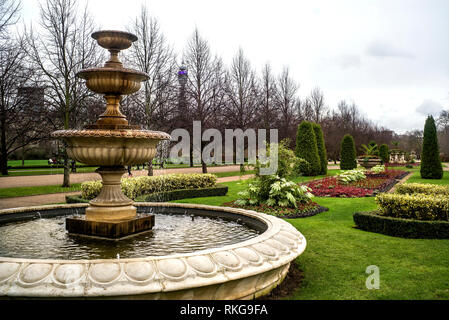 Fountain, trees and flower beds,grey sky,  Avenue Gardens at Regents Park,London, England, UK. - Stock Photo