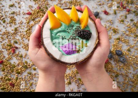 Spirulina bowl smoothie in coconut blackberry mango and chia seeds. - Stock Photo