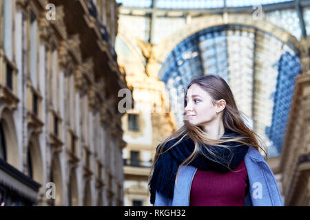 Girl daydreaming while walking inside of Galleria Vittorio Emanuele II in Milan Italy - Stock Photo