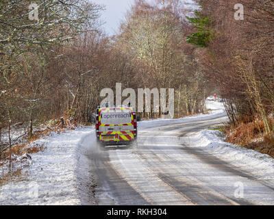 BT Openreach van on the A831 road in winter when partially covered in snow, Glen Urquhart, Highland, Scotland. - Stock Photo