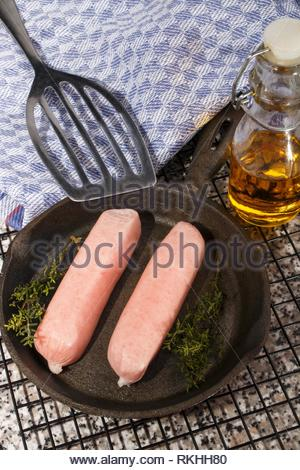 home made raw british sausages with herbs in a cast iron pan. - Stock Photo