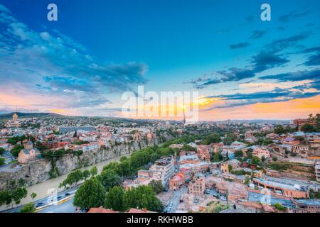 Evening View Of Tbilisi At Colorful Sunset. Georgia. Summer Cityscape. Left Side Of The Photo Is Visible The Metekhi Church. Right Side Of The Photo - Stock Photo