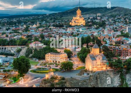 Evening View Of Tbilisi, Georgia. Summer Cityscape. On Photograph Visible Holy Trinity Cathedral Of Tbilisi And Metekhi Church. - Stock Photo