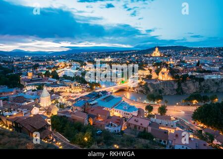 Scenic Top View Of Summer Evening Cityscape Of Tbilisi, Georgia In Illumination Lights With All Famous Landmarks, Sightseeings. Dramatic Blue Cloudy - Stock Photo