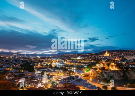Scenic Top View Of Tbilisi, Georgia In Bright Evening Illumination With All Famous Landmarks, Sightseeings. Dramatic Blue Cloudy Sky Background. - Stock Photo