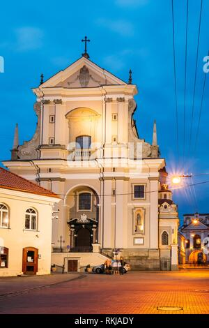 Vilnius, Lithuania. View Of Ancient Early Baroque Catholic Church Of St. Teresa On Illuminated Ausros Vartu Street. Famous Landmark Of Old Town, - Stock Photo