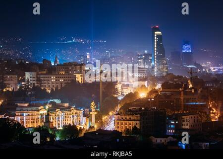 Tbilisi, Georgia. Construction Development Of Modern Architecture On Background Of Urban Night Cityscape. Evening Night Scenic Aerial View Of City - Stock Photo